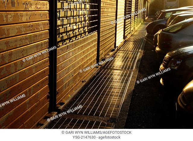 Row of Closed shutters on shop fronts at sunset in rome italy