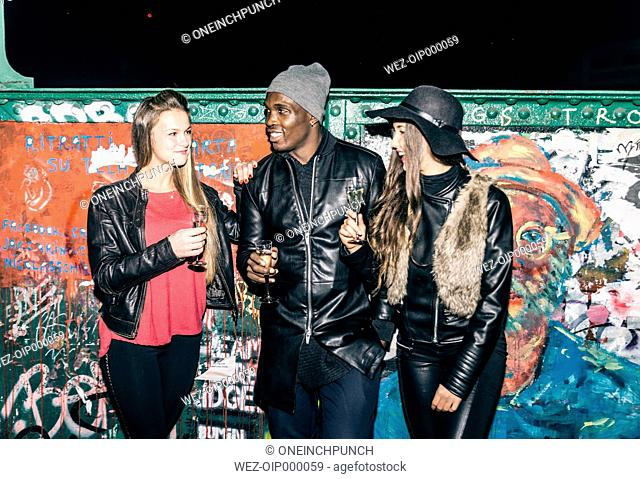 Friends holding champagne glasses standing at graffiti wall at night
