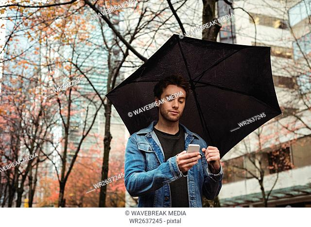 Man using mobile phone and holding umbrella