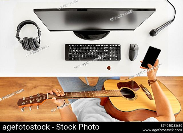 young man with guitar and smartphone at table