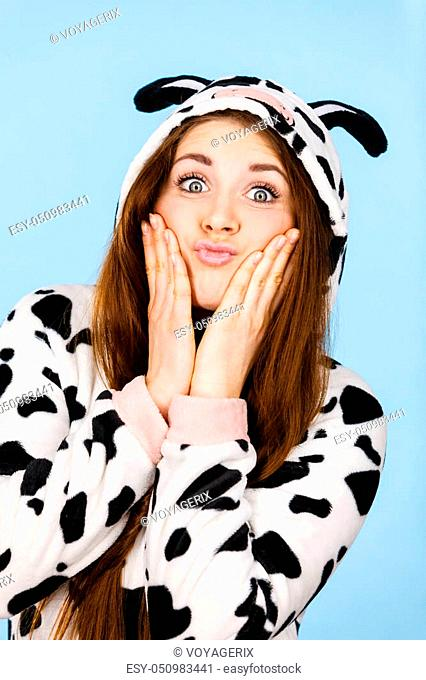 Happy teenage girl in funny nightclothes, pajamas cartoon style making silly face, positive face expression, studio shot on blue