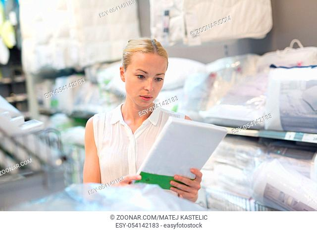 Pretty, young woman choosing the right bed sheets for her bed in modern home furnishings store