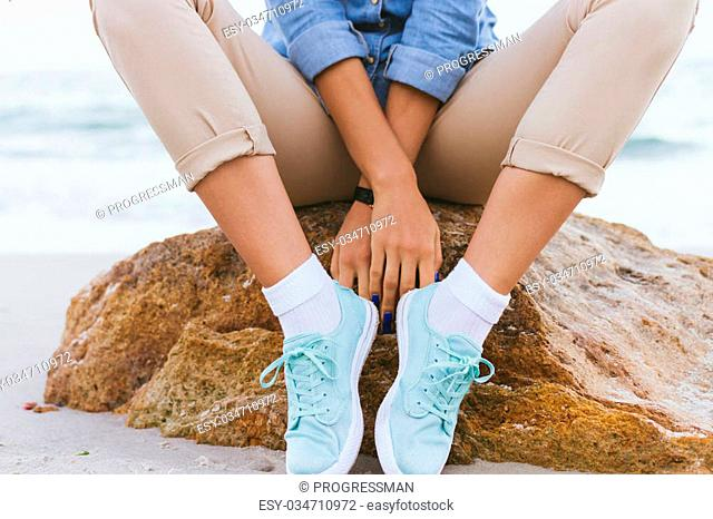 Woman in beige pants and a denim shirt and turquoise sneakers sitting on a rock by the sea. Shirt sleeves rolled up, watch on her arm, a blue manicure