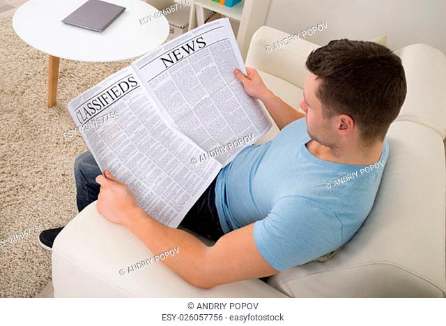 High angle view of mid adult man reading newspaper on sofa at home