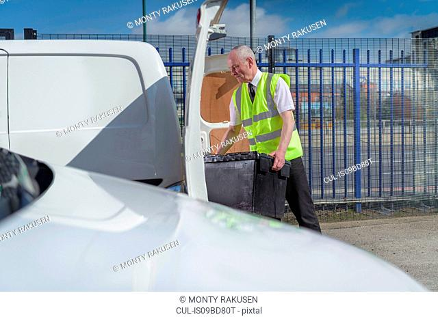 Senior delivery driver loading all electric van