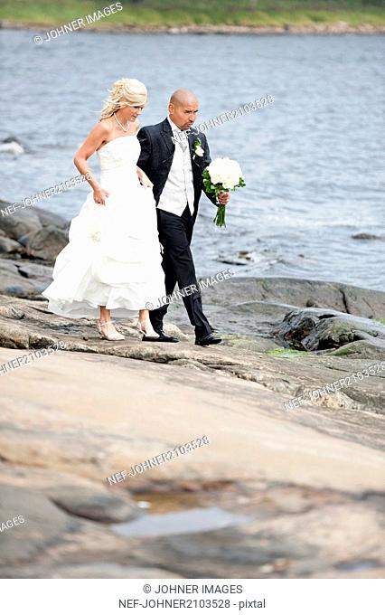 Bridal couple walking on rocky coast