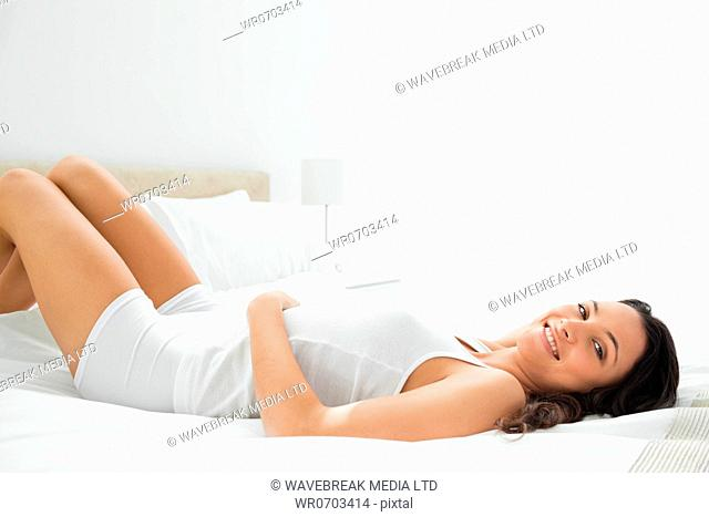 Pleasing smiling woman lying in her white bed on a white room