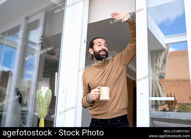 Happy man waving while standing by sliding door at home