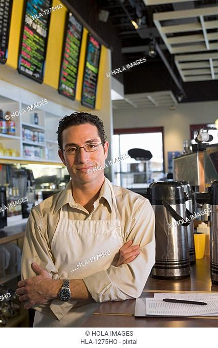 Portrait of a male store clerk standing in a coffee shop