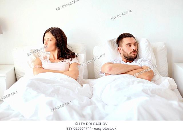 people, relationship difficulties and family concept - unhappy couple having conflict in bed at home