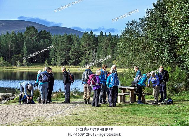 Elderly walkers meeting and preparing to go hiking along Loch Morlich in the Cairngorm mountains, Scottish Highlands, Scotland, UK