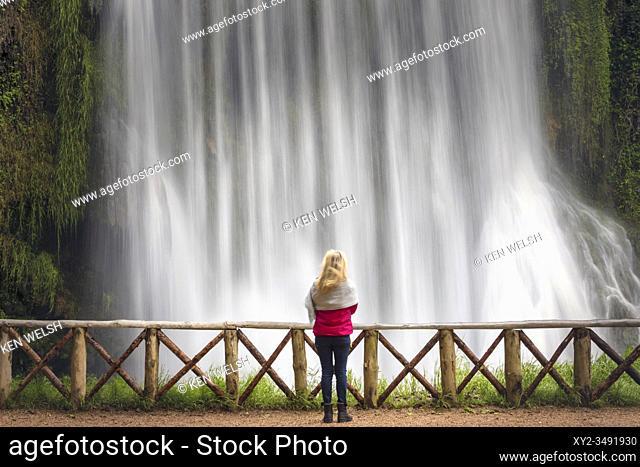 Woman standing in front of La Caprichosa waterfall in Parque Natural del Monasterio de Piedra, Zaragoza Province, Aragon, Spain