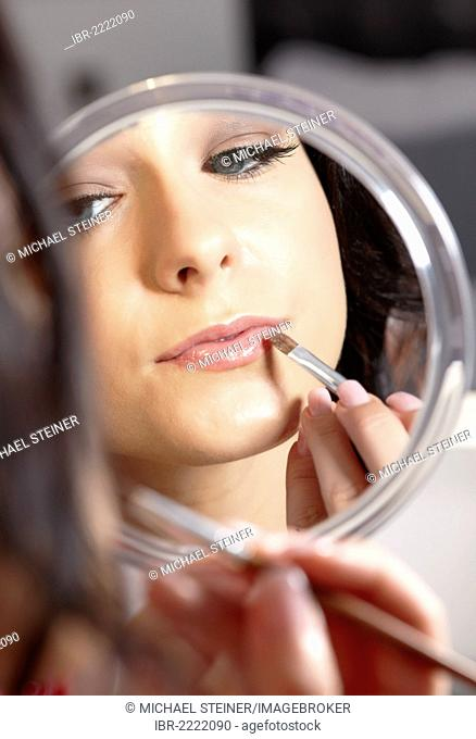 Young woman holding a hand mirror and a lipstick brush