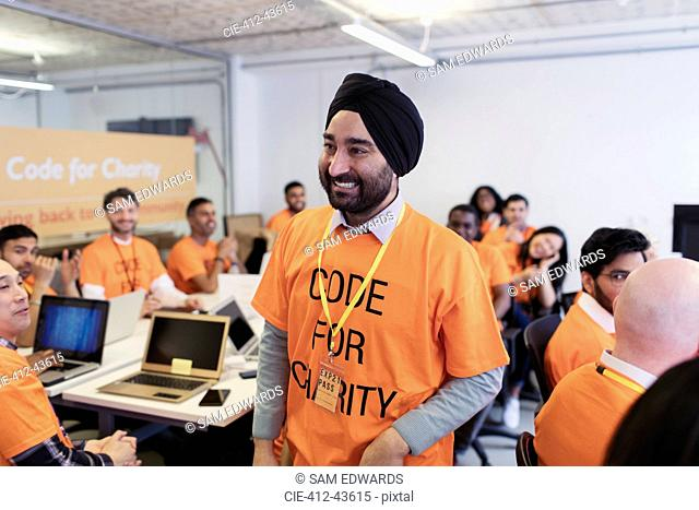 Happy, confident hacker in turban coding for charity at hackathon