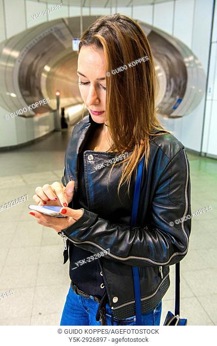 Rotterdam, Netherlands. Attractive brunette entering Wilhelminapier Subway Station catching her train down town