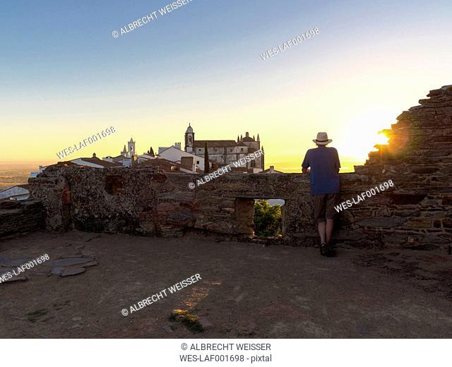 Portugal, Senior man watching sunrise at Castel de Monsaraz