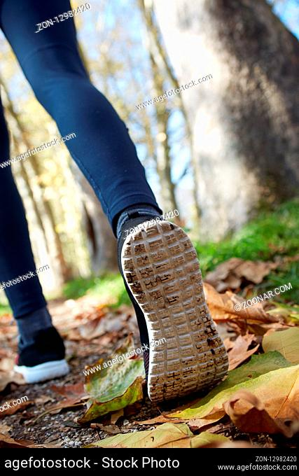 close up of feet of a runner running in autumn leaves training for marathon and fitness healthy lifestyle