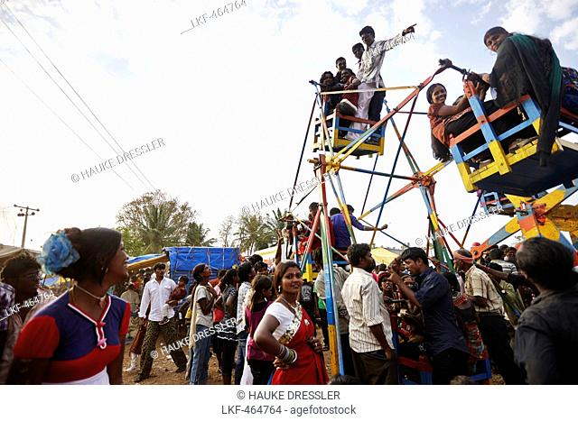 People in a manual small ferris wheel, Angadehalli Belur, Karnataka, India