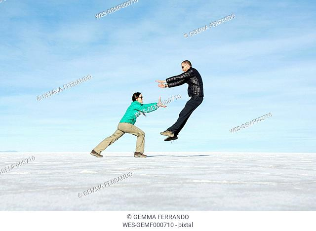 Bolivia, Salar de Uyuni, woman kicking man