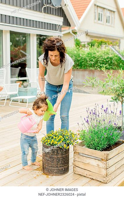 Mother with daughter watering plants on patio