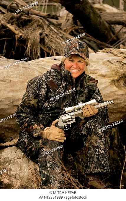 Female big game hunter with a scoped handgun