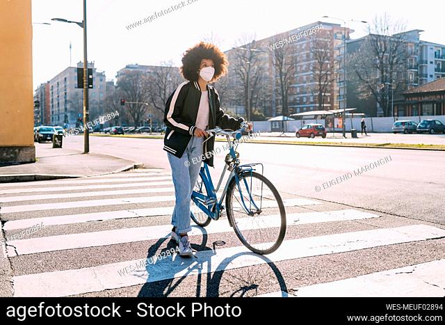 Woman wearing protective face mask walking with bicycle on road in city