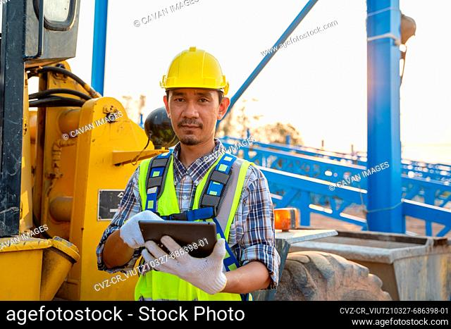 Engineering wearing a yellow safety helmet standing In front of