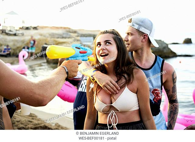 Crete, Chersonisou, Beach Party, woman getting tequila shot with water gun, man embracing her from behind