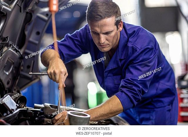 Car mechanic in a workshop repairing car