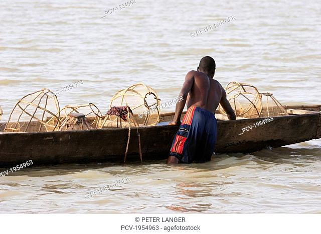 Fisherman and his nets on a boat in Lake Debo, formed by the seasonal flooding of the Niger River, Mali