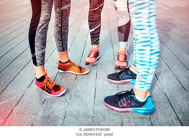 Legs of three female runners standing on wooden pier