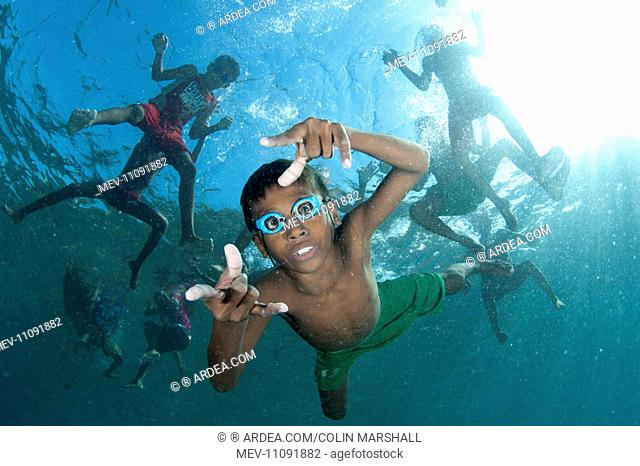 Underwater boys wearing goggles playing in the water