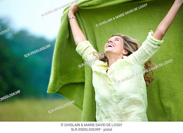 Woman holding blanket outdoors