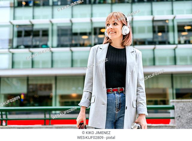 Woman with headphones in the city on the go