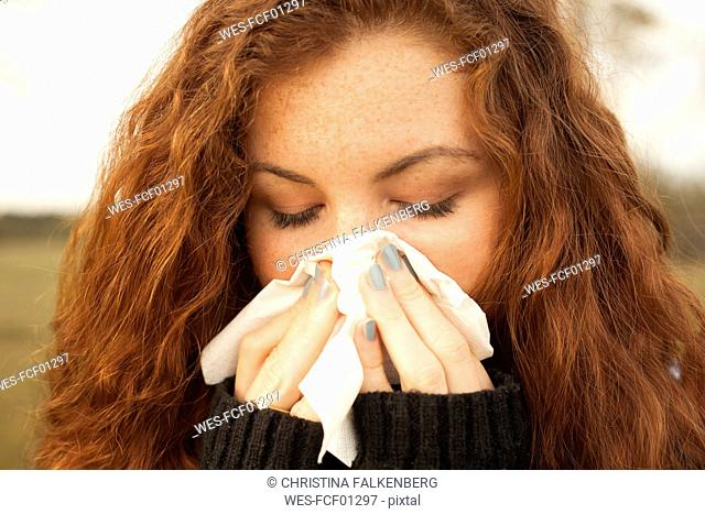 Redheaded young woman blowing nose in nature