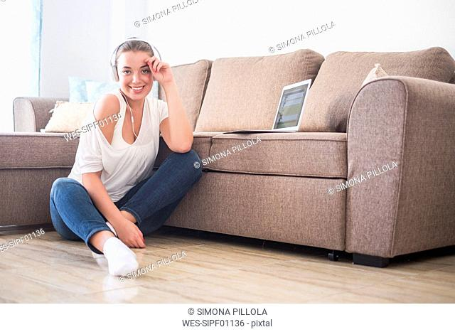 Smiling young woman sitting on the floor of living room listening music with laptop and headphones