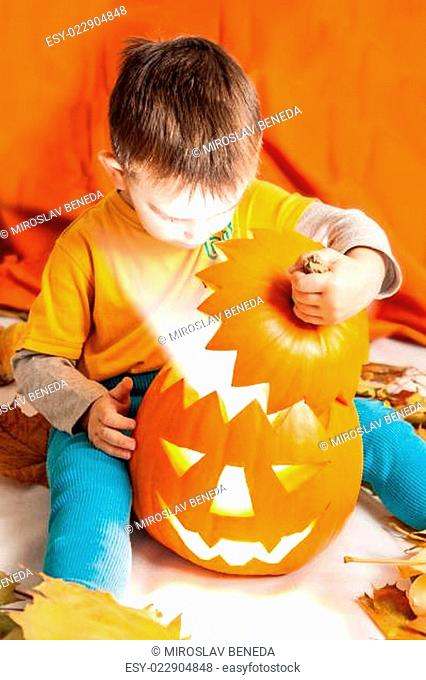A cute photograph of a boy and her lighting Halloween pumpkin