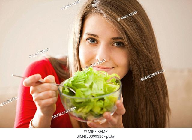 Caucasian woman eating salad