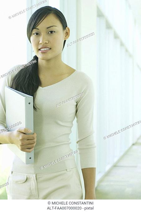 Young woman walking in hallway, carrying file