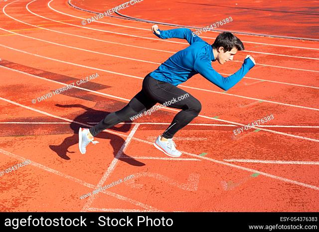 Runner starting his sprint on running track in a stadium