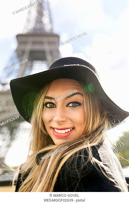 France, Paris, portrait of smiling woman in front of Eiffel Tower