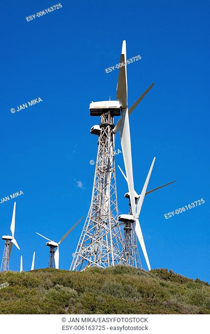 Wind turbines on the green hill with blue sky Tarifa, Cadiz, Andalusia, Spain
