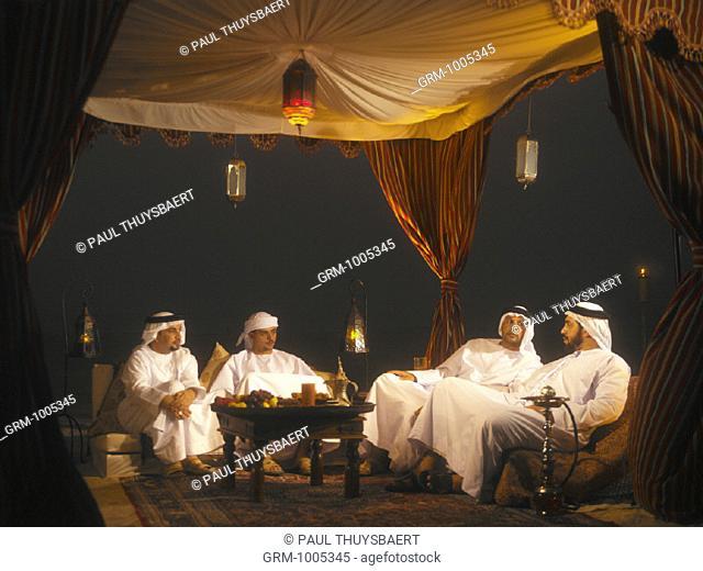 Ramadan: men sitting in Arabian tent for Iftar (fast-breaking meal after sunset)
