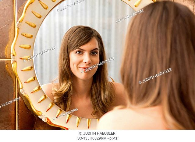woman in front of mirror, laughing