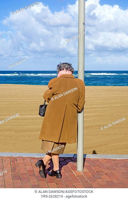 Elderly woman leaning on post overlooking beach and sea