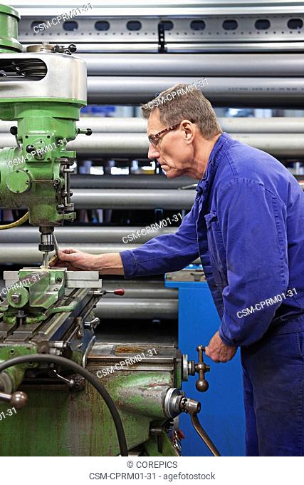 Middle aged man behind an industrial grinding machine in a mechanical workshop