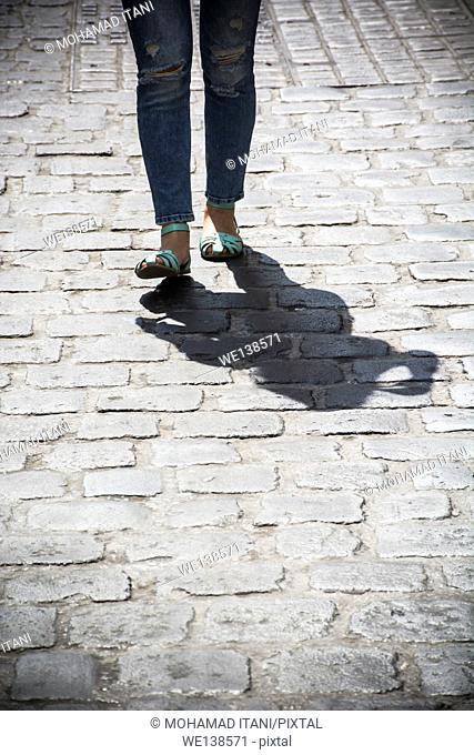 Close up of a young woman walking on a cobbled road