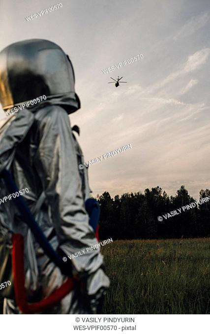 Spaceman exploring nature, watching helicopter
