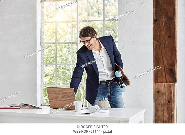 Laughing businessman with skateboard using laptop on desk