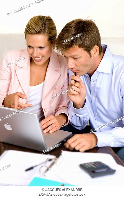 Couple paying bills with laptop on sofa